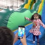 Girl playing at the Hamilton Plastics Christmas Party in a Bounce House.